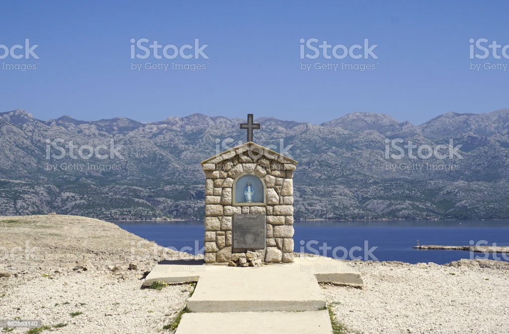 Small chapel with Mary statue on the Island of Pag Dalmatia, with Velebit mountain in the background in Croatia stock photo