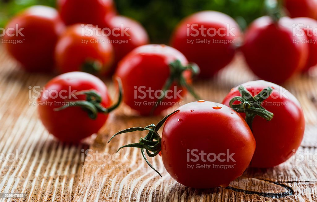 Small cherry tomatoes on wooden background, selective focus stock photo