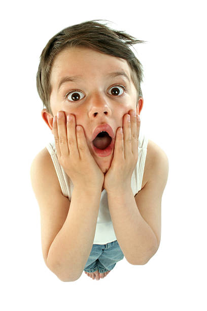 A small child cupping his face in utter shock stock photo