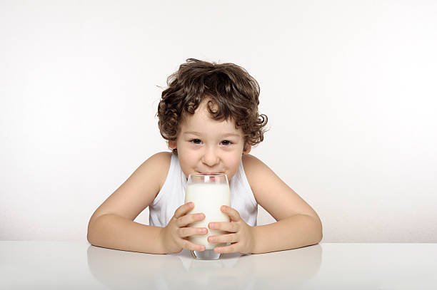 Small child drinking a glass of milk stock photo