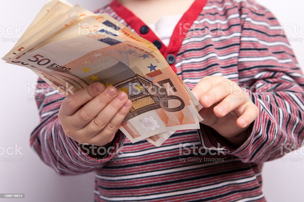 Small child hand hold fifty euros banknotes stock photo