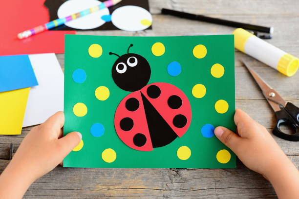 small child holds a ladybug card in his hands. child created a cardboard ladybug card. stationery on a desk. cardboard circle crafts for teaching kids to cut and glue. developing children motor skills - kids holding hands zdjęcia i obrazy z banku zdjęć