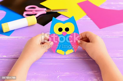 istock Small child holds paper owl in his hands 597954786