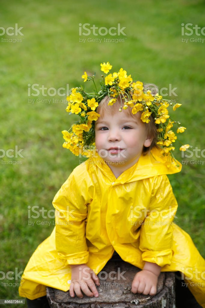 26d397c5f A Small Child In A Yellow Raincoat And A Buttercup Wreath Sits On A ...