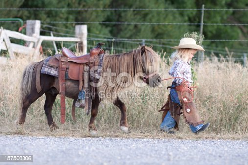 Little girl with cowboy hat, walking with her little horse.