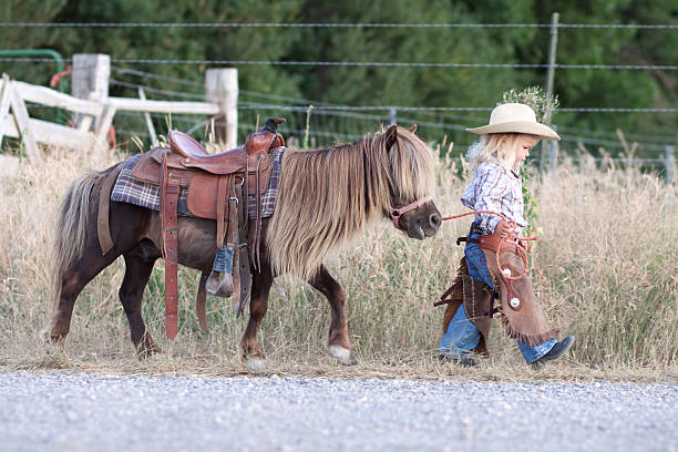 Small child in cowboy outfit with cute hairy pony on a lead Little girl with cowboy hat, walking with her little horse. pony stock pictures, royalty-free photos & images