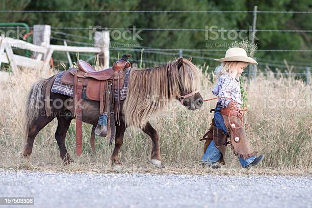 Photo of Small child in cowboy outfit with cute hairy pony on a lead
