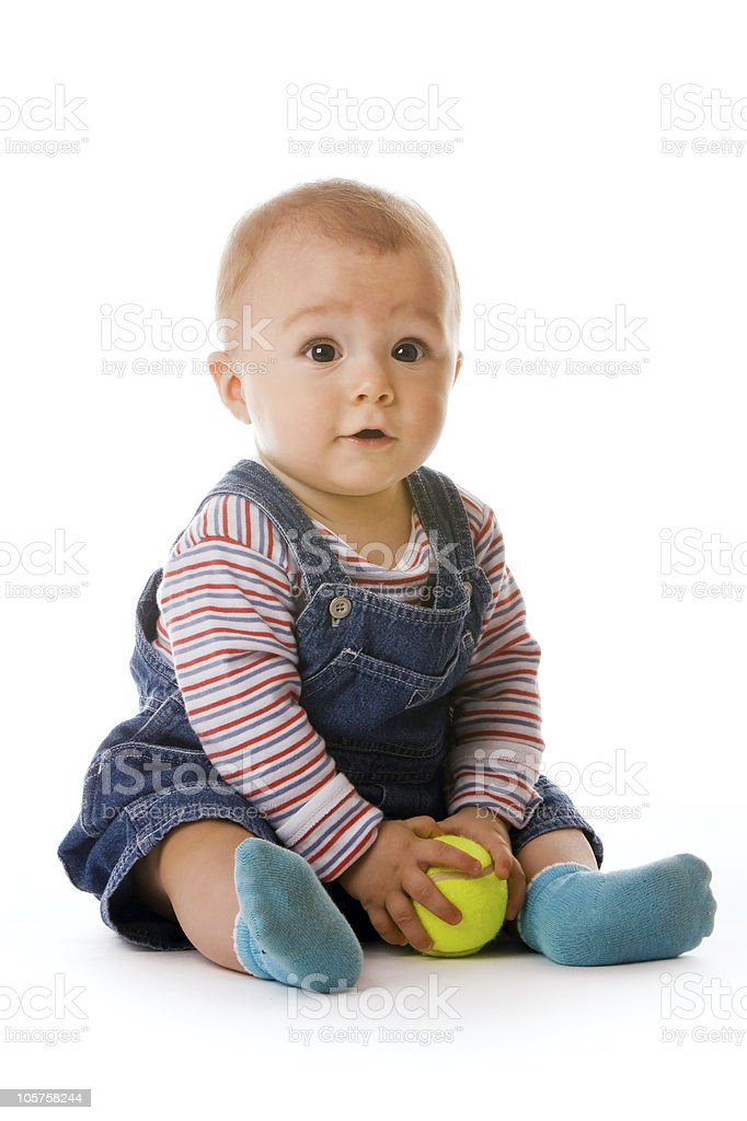 Small child in jeans holding tennis ball stock photo