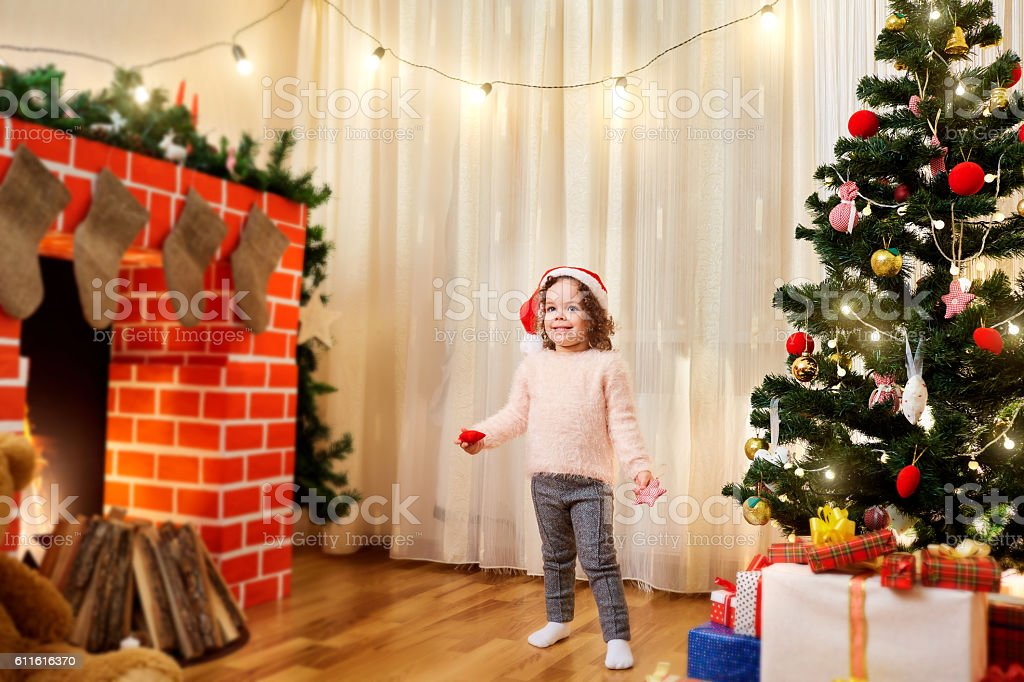 Small child in santa hat at Christmas  decorated room smil stock photo