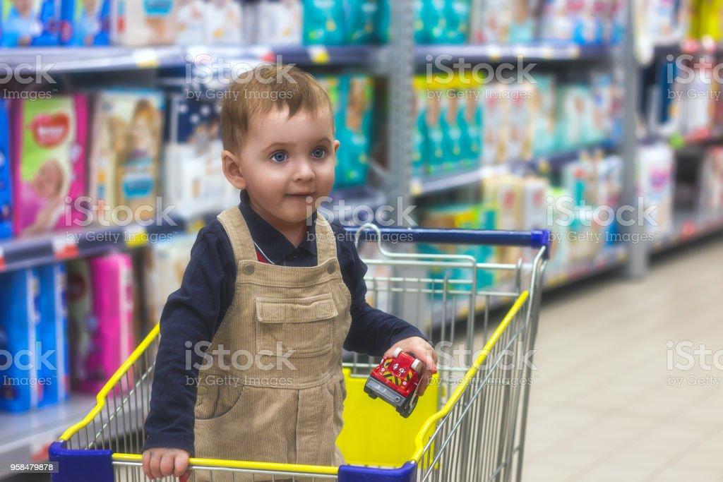 ca10e09ae3 Criança pequena está de pé em um carrinho de compras na loja e escolher  brinquedos.