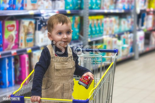 926078666 istock photo Small child is standing in a grocery cart in the store and choosing toys. 958479878