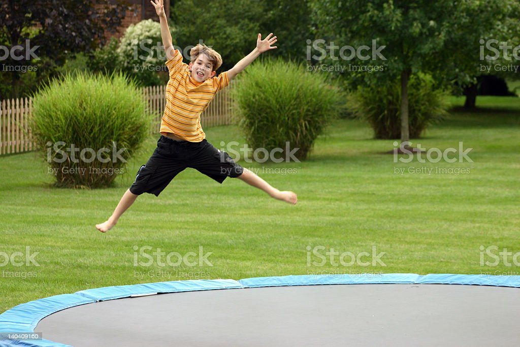A small child jumping on a trampoline stock photo