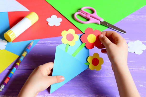 small child makes paper crafts for mother's day or birthday. small child doing paper flowers for mom. simple and nice gift idea. scissors, glue stick, flowers templates, pencil on a wooden table - kids holding hands zdjęcia i obrazy z banku zdjęć