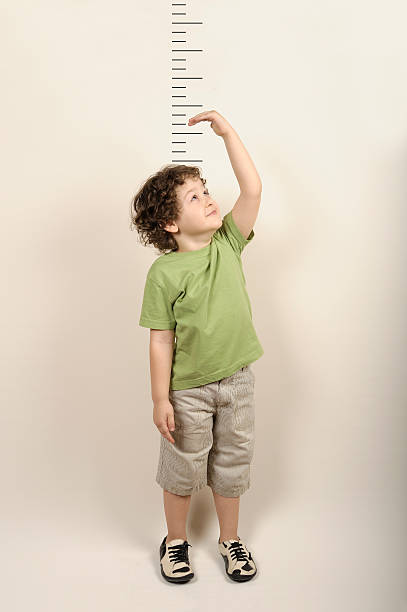 small child measuring himself standing up - height measurement stock photos and pictures