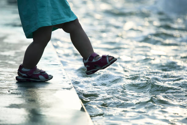 small child on the pavement makes a dangerous step into the water stock photo
