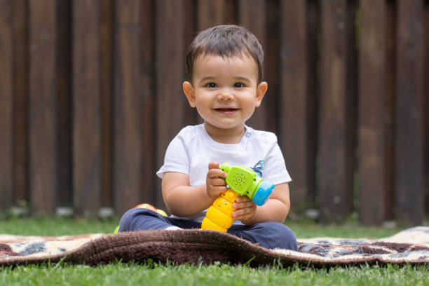 Small child playing on the grass stock photo