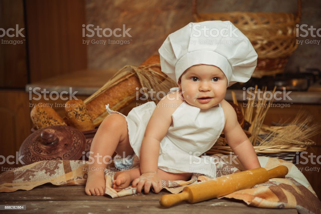 A small child posing as a fashion model in the suit of a cook sitting in the kitchen. Place for text stock photo