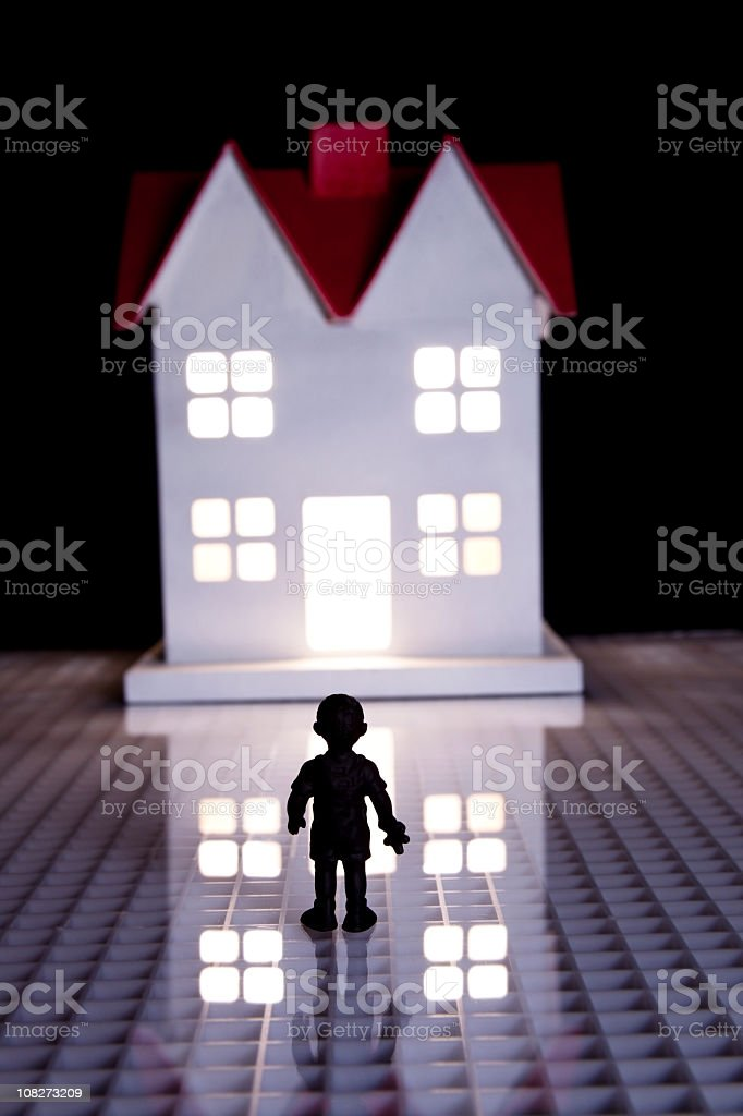 Small child standing outside house glowing from inside royalty-free stock photo