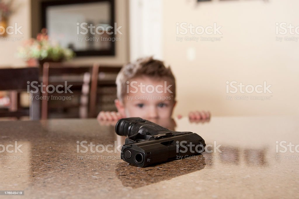A small child staring at a hand gun within reach on a table stock photo
