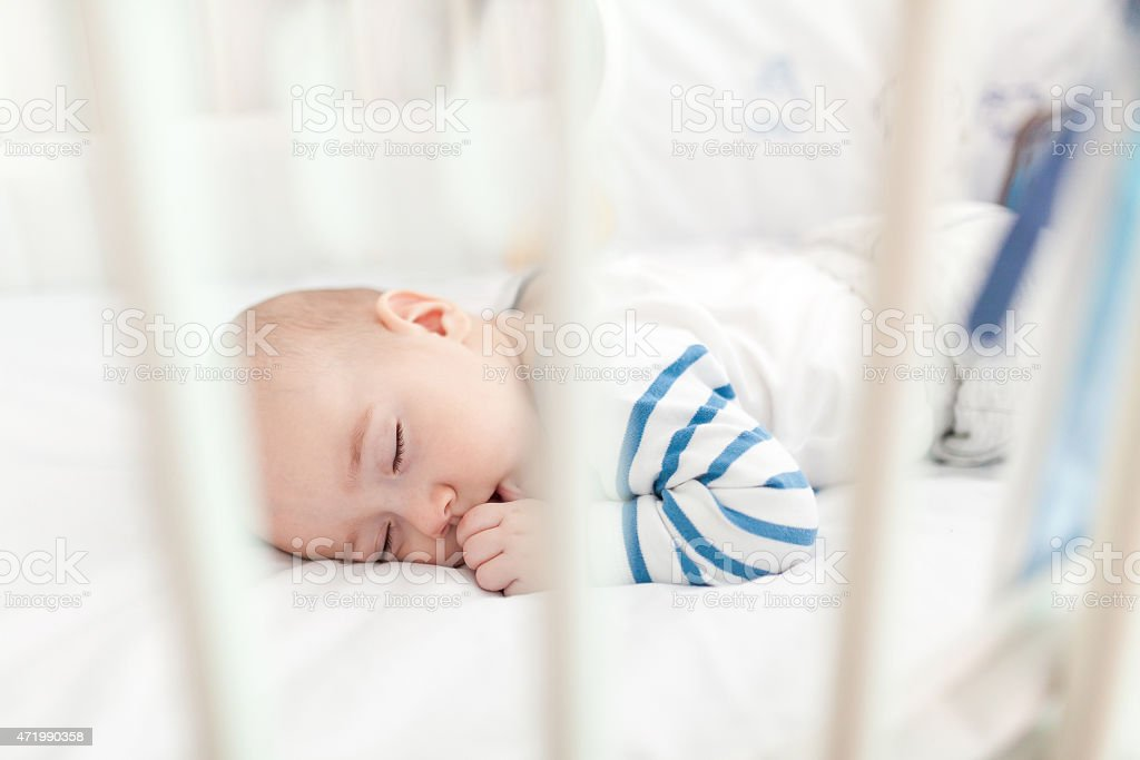 A small child takes a nap in a white blanketed crib stock photo