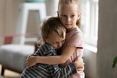 Cute little kids siblings hug and cuddle at home show love and care, small girl sister embrace hurt upset preschooler brother, take care of cousin, family relationships, children support concept