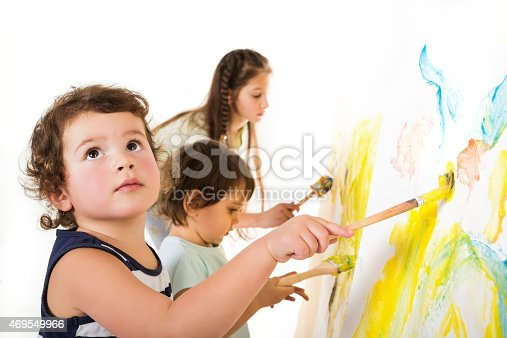 istock Small children draw paints on a paper wall 469549966