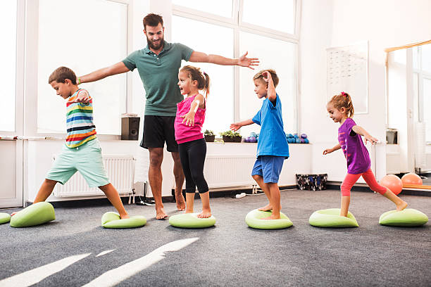 Small children walking on Pilates balls on training class. stock photo