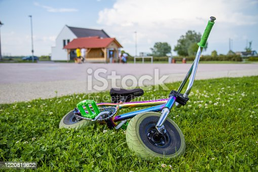 A colourful small children's two-wheeled bicycle lies on the grass, next to the playground