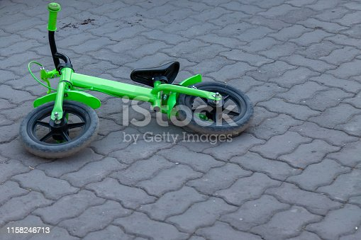 A small children's two-wheeled bicycle of green color lies on its side on a street tile of gray color without people and nobody is left around after a whim and crying.