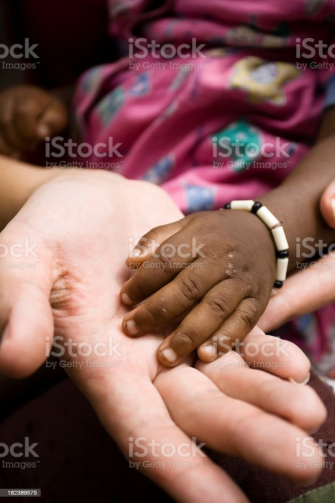 A small child's hand inside an adults hand stock photo