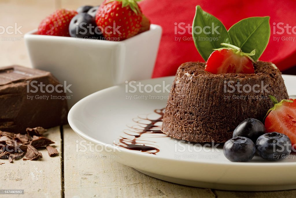 Small chocolate dessert with berries on a ceramic plate stock photo
