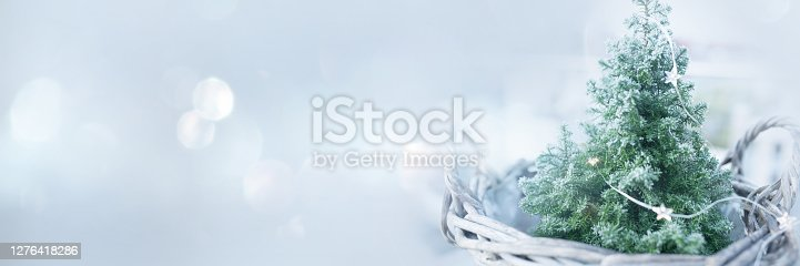 Small christmas tree with fairy light for festive greetings. Horizontal background with silver bokeh and short depth of field for a christmas greeting card.