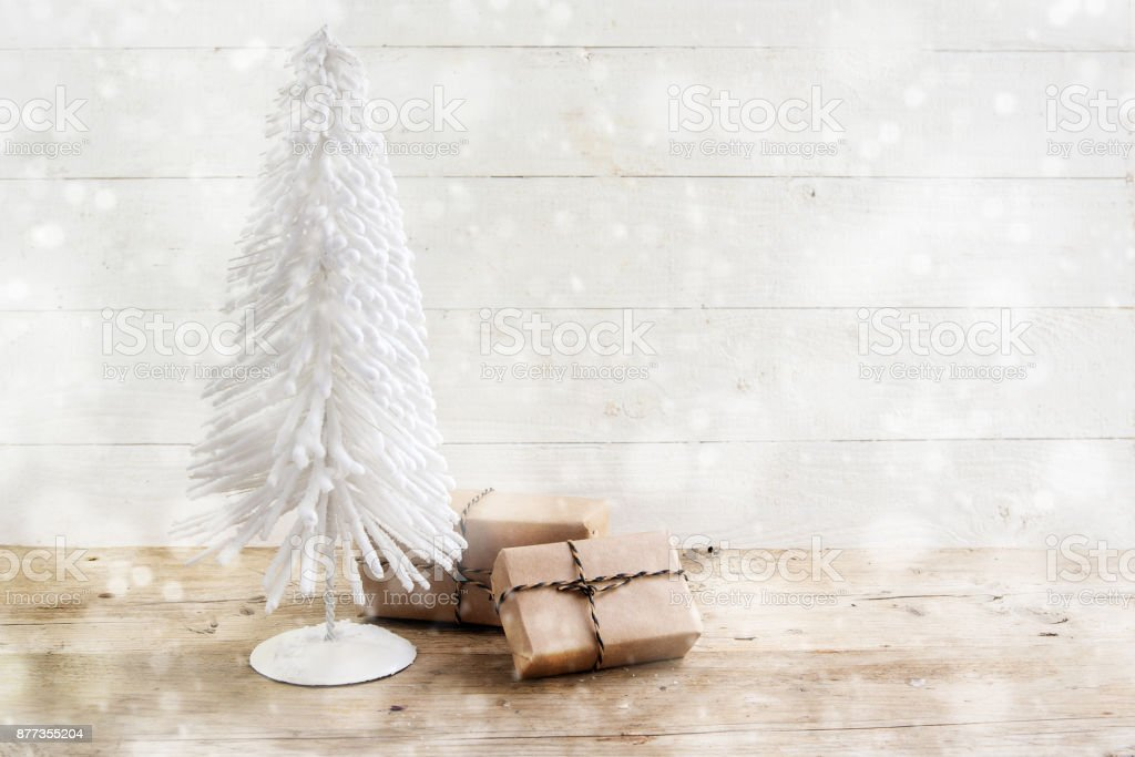 small christmas tree from white wire and gifts in kraft paper on a rustic wooden table