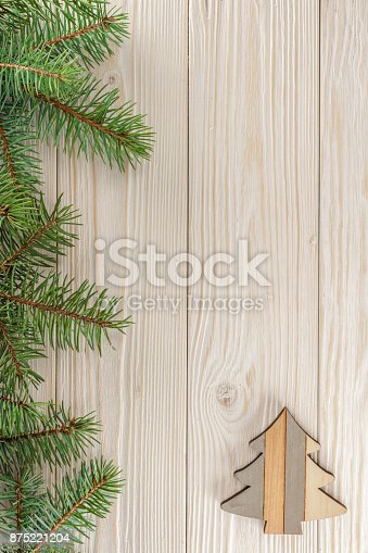 A small Christmas tree on white wooden background. The frame of spruce branches. The view from the top. Place for Your text.