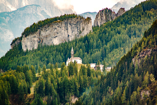 Small church with a chapel on a background of a mountain forest in the Italian Dolomite Alps, Italy.