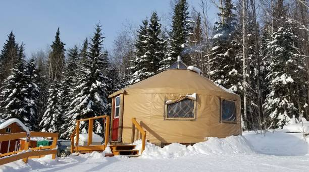 Small Circular Housing, a Yurt, in a Snowy Evergreen Setting stock photo