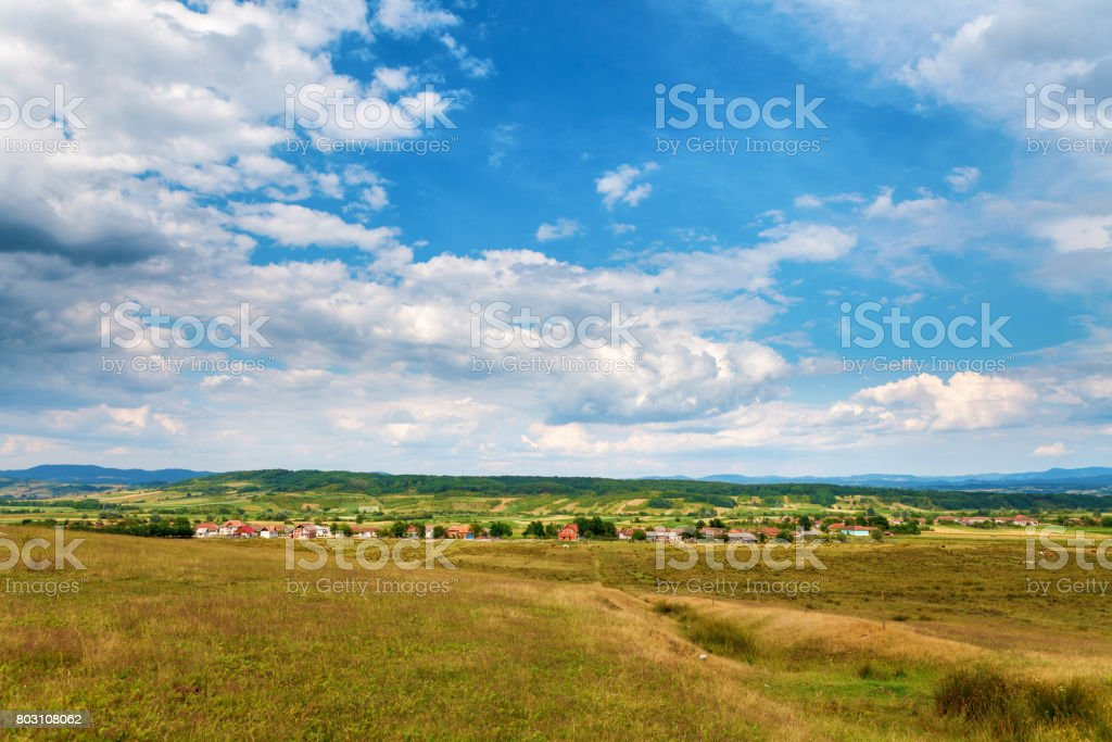 Small city by the mountains under blue cloudy summer sky, somewhere in Romania stock photo