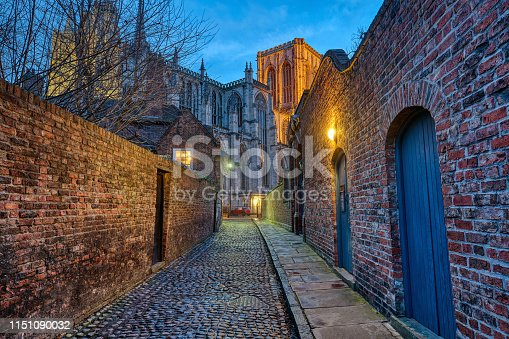 Small cobbled alleyway in York at night with the famous Minster in the back