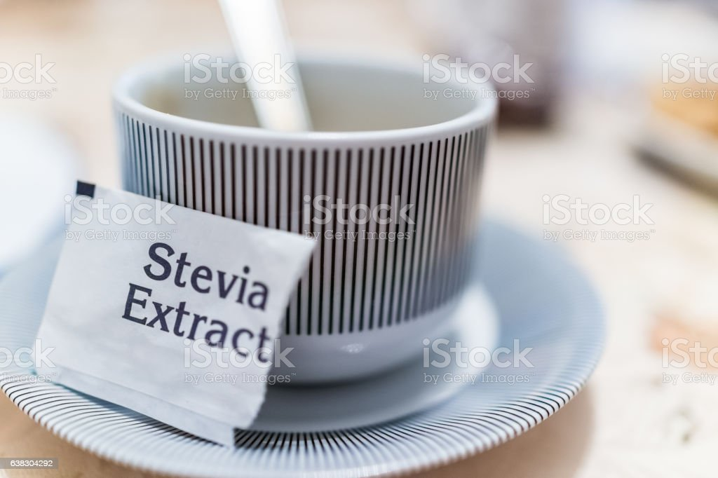 Small coffee cup on plate with stevia extract packet - foto de acervo