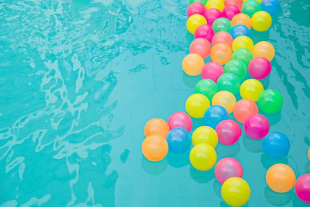 Petits ballons de plage colorées flottant dans le concept abstrait de piscine pour piscine vacances d'été et fête. - Photo