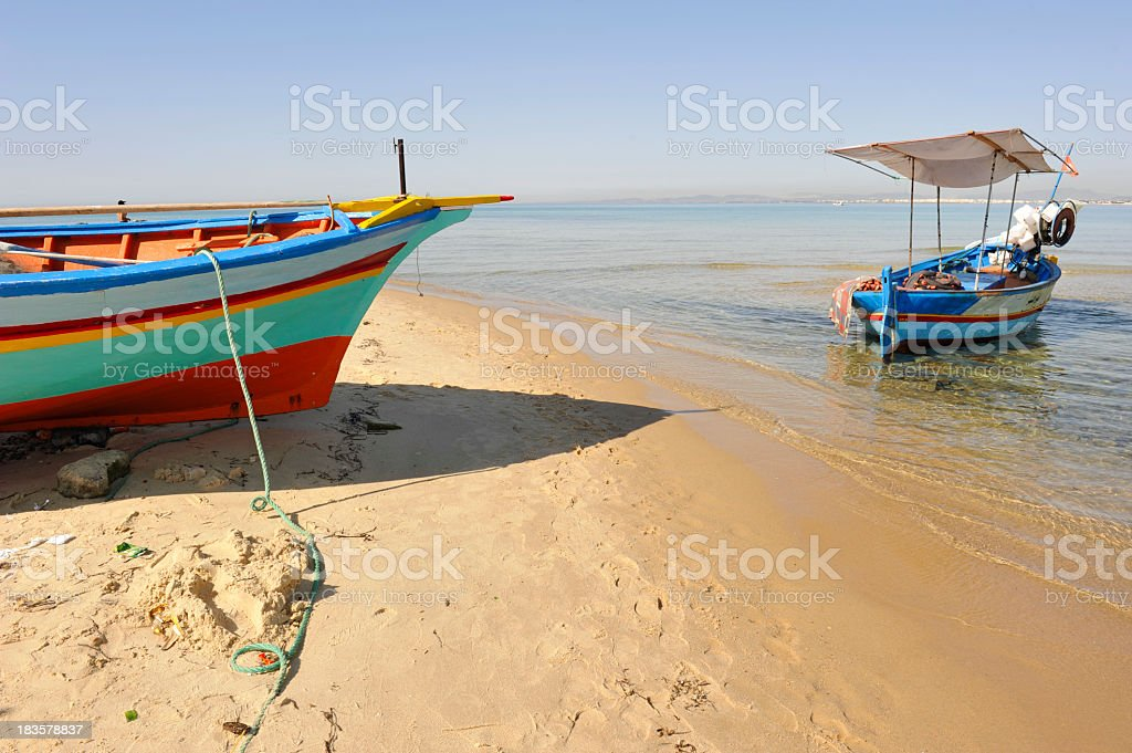 Small colorful fishing boats on shore and beach sand stock photo