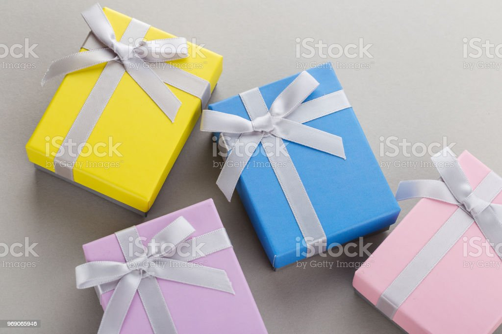 Small Colorful Gift Boxes With Ribbon Bows On Gray Background
