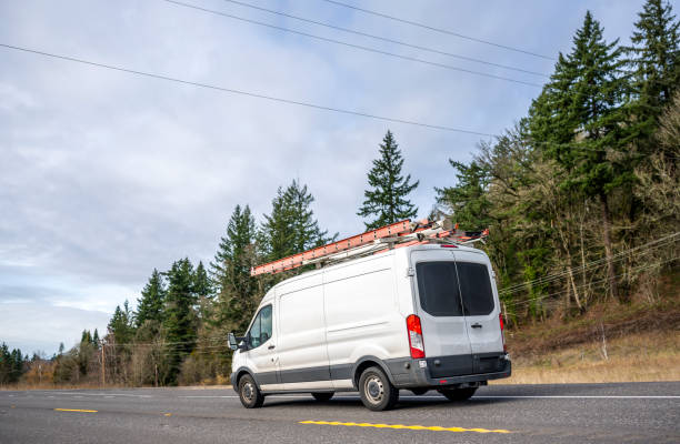 Small compact commercial cargo mini van with ladders on the roof running on the road with trees on the hill stock photo