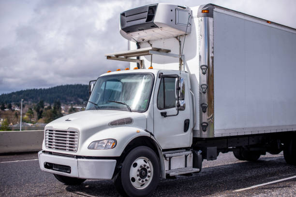 Small compact rig semi truck with refrigerated box trailer running on the road for local deliveries stock photo