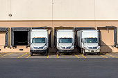 Small compact mobile rigs semi trucks with box trailers for local shipping and delivery standing in row at warehouse docks waiting for loading commercial cargo