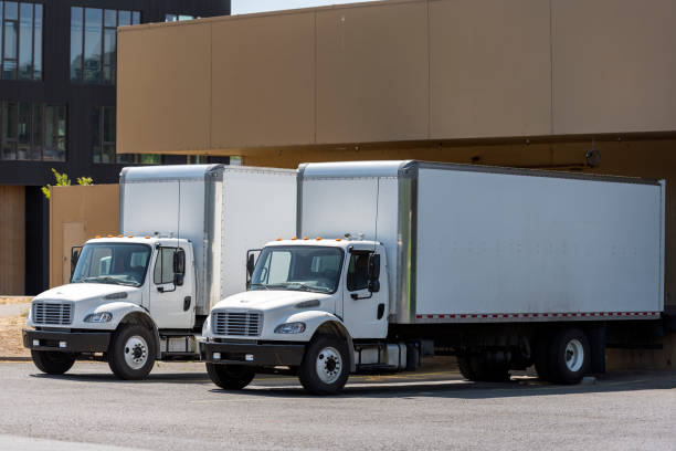 Small compact rigs semi trucks with long box trailers standing in warehouse dock loading cargo for delivery stock photo