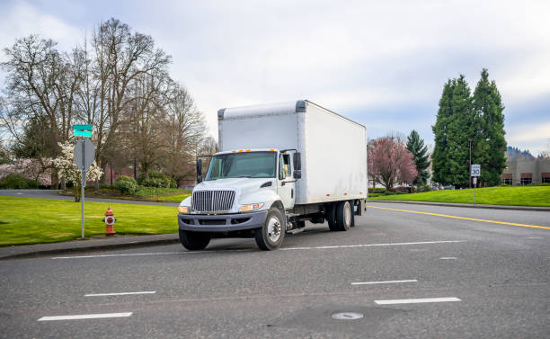Small compact semi truck with cube box trailer transporting commercial cargo driving on the street of urban city in spring time with blooming trees stock photo