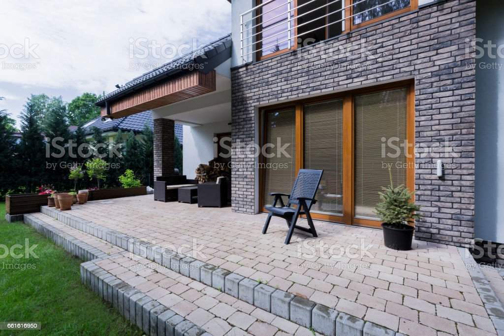 Small concrete terrace with furnitures in modern house with brick...