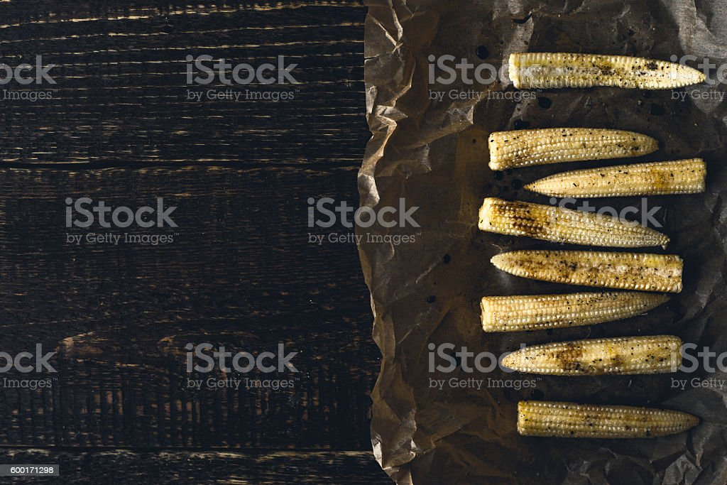 Small corn on parchment  at right of wooden table Lizenzfreies stock-foto