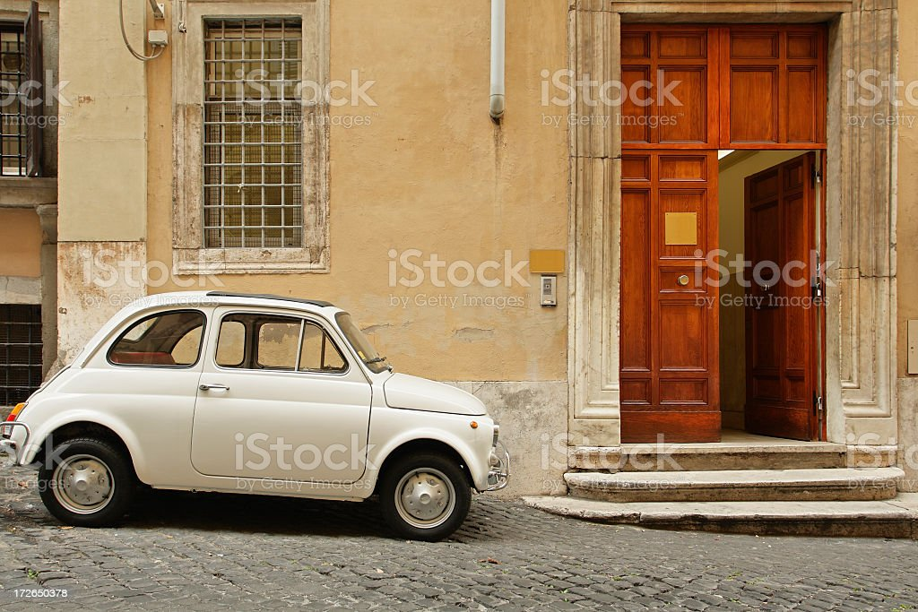 Small coupe parked near a doorway on a cobblestone street royalty-free stock photo